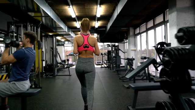 young woman walking through gym and exercising on lateral pull-down weights exercise machine. - lateral pull down weights stock videos & royalty-free footage
