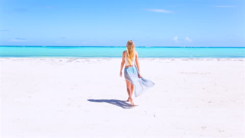 ms young woman walking through palm trees to tropical beach - tag stock-videos und b-roll-filmmaterial