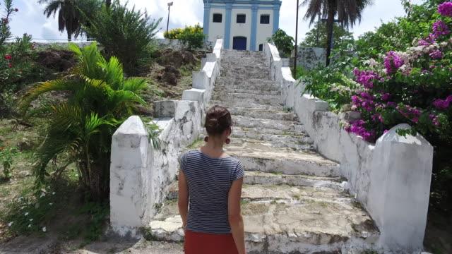 vídeos de stock, filmes e b-roll de young woman walking to a colonial church - vista traseira