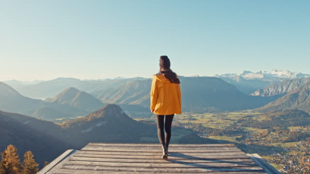 vídeos de stock e filmes b-roll de ms young woman walking to edge of platform overlooking sunny, scenic mountain landscape view, loser mountain, austria - vista traseira