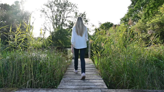 young woman walking to end of short pier in rural area - west sussex stock videos & royalty-free footage
