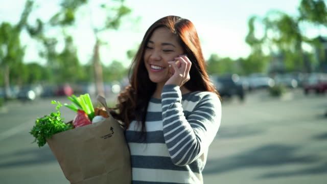 ms ts sm young woman walking to her car holding a shopping bag - paper bag stock videos & royalty-free footage