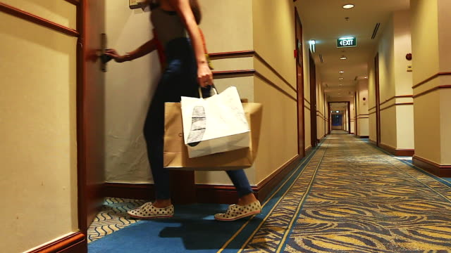 Young woman walking to her room at the hotel after finished shopping.