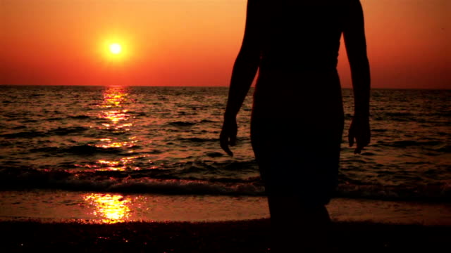 Young Woman Walking Towards The Sea