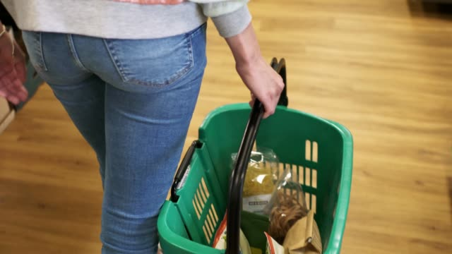 young woman walking trough the supermarket with a full shopping basket - shopping basket stock videos and b-roll footage