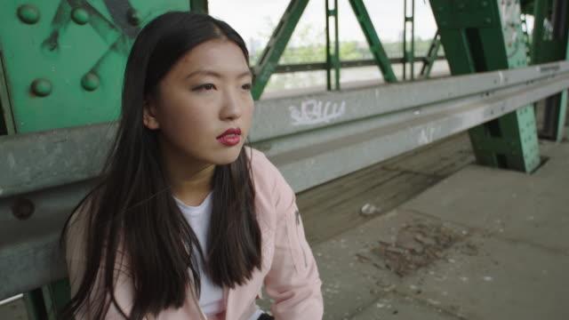 Young woman walking under bridge. Loneliness