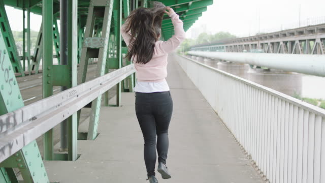 Young woman walking under bridge