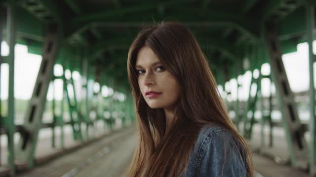Junge Frau, die unter Brücke