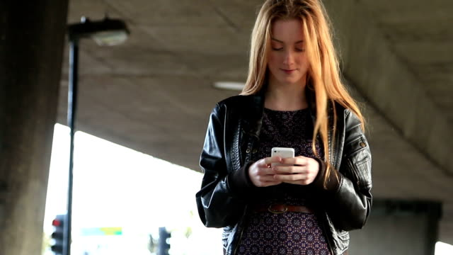 Young woman walking using smartphone.