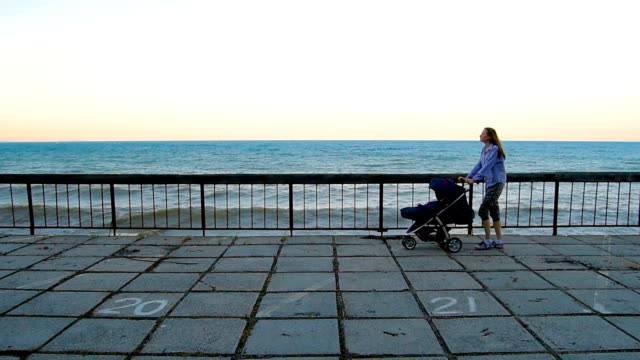 young woman walking with baby in stroller - pushchair stock videos and b-roll footage
