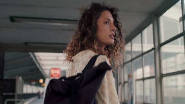 young woman walking with backpack into urban railway station in berlin - rucksack stock-videos und b-roll-filmmaterial