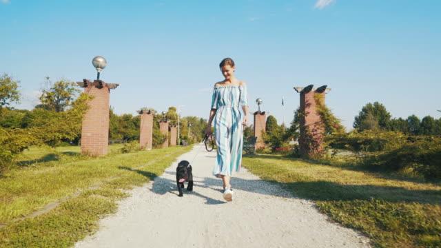 vidéos et rushes de jeune femme qui marche avec son chien. - femme soumise