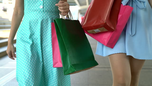 Young woman walking with shopping bag shooting shot with below angle.