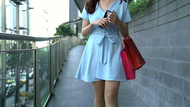 ショッピング バッグの撮影と一緒に歩いている若い女性は、角度の下で撮影。 - 買い物袋点の映像素材/bロール