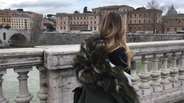 若い女性は、市内の橋を渡って歩きます - 毛皮のコート点の映像素材/bロール