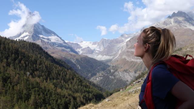 young woman walks along hillside, matterhorn distant - rucksack stock videos & royalty-free footage