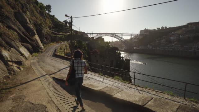 young woman walks along river - porto, portugal - porto district portugal stock videos & royalty-free footage
