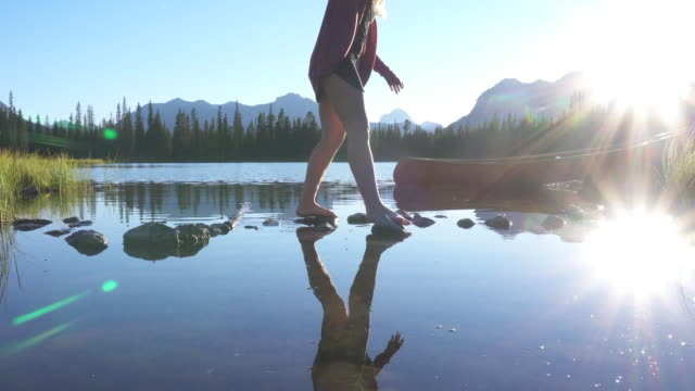 young woman walks along stepping stones at mountain lake - stepping stone stock videos & royalty-free footage