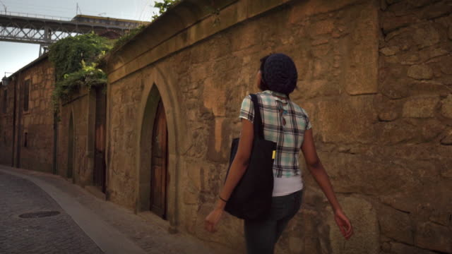 young woman walks along stone wall - porto, portugal - porto district portugal stock videos & royalty-free footage