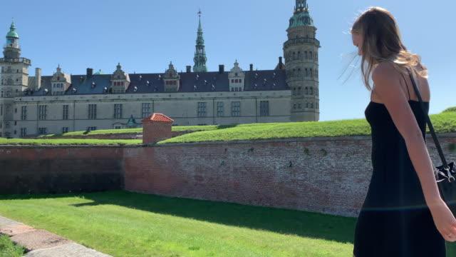 vídeos de stock e filmes b-roll de a young woman walks along the ramparts of kronborg castle, helsingør (helsingör), denmark - vala