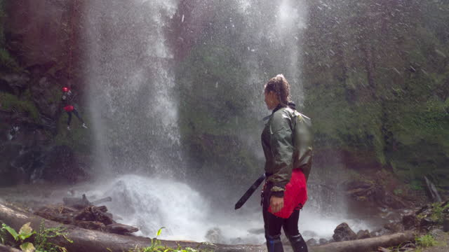 young woman walks at base of massive waterfall watching another woman rappel down cliff - galapagos islands, ecuador - south pacific ocean stock videos & royalty-free footage