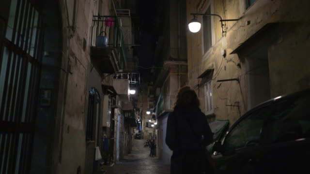 Young woman walks at night in Naples, Italy