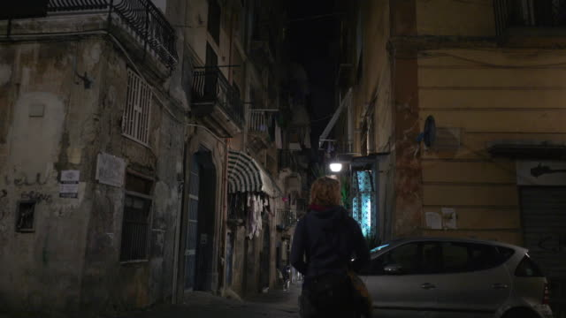 young woman walks at night in naples, italy - cappuccio video stock e b–roll