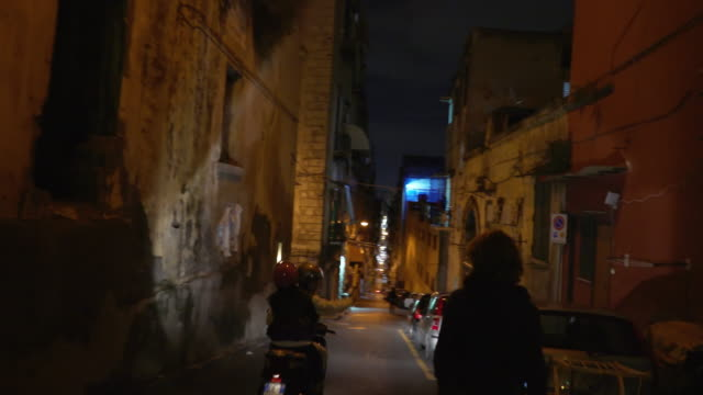 young woman walks at night in naples, italy - motocicletta video stock e b–roll