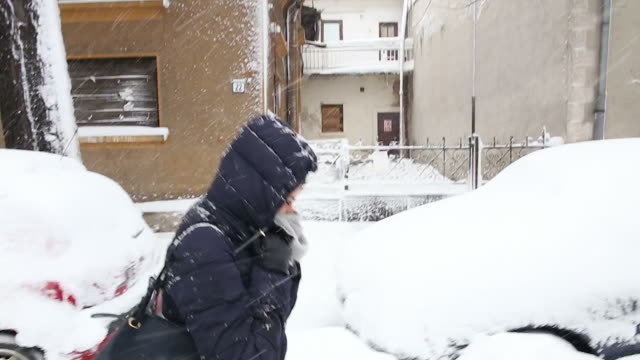 giovane donna cammina nella neve via. - glove video stock e b–roll