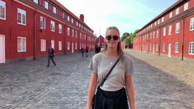 a young woman walks inside the grounds of kastellet (the citadel), copenhagen - öresundregion stock-videos und b-roll-filmmaterial