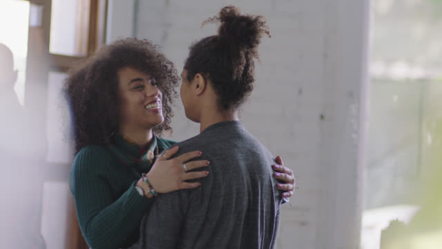 vídeos y material grabado en eventos de stock de ms slo mo. young woman walks into coffee shop and wraps arms around boyfriend with a hug as he lifts her up. - de ascendencia mixta
