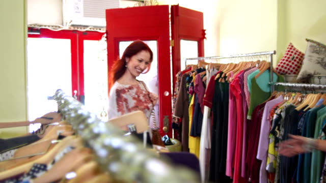 HD: Young Woman Walks Into Fashion Boutique