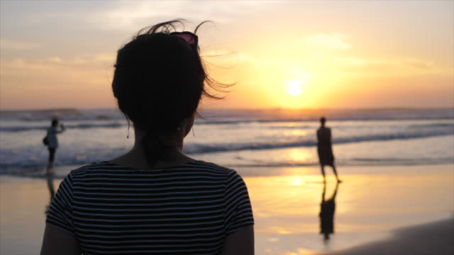 a young woman walks on the beach at sunset. - indonesia beach stock videos & royalty-free footage
