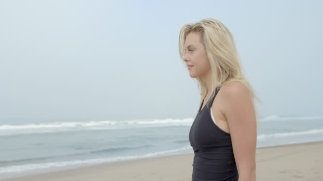 young woman walks on the sand as waves break on beach in malibu 4k - skirt stock videos & royalty-free footage