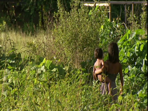 young woman walks through dense undergrowth carrying small child amazon rainforest venezuela - two generation family stock videos & royalty-free footage