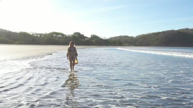 young woman walks through gentle surf, wearing beach kimono - パレオ点の映像素材/bロール