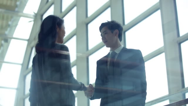 PAN MS Young woman walks to greet young man with a handshake in a modern office