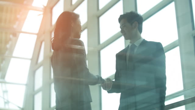 MS Young woman walks to greet young man with a handshake in a modern office