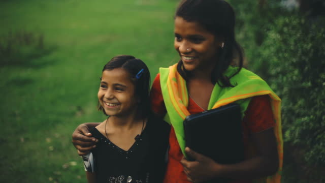 young woman walks together with her child sister holding a laptop in a park. - indian ethnicity stock videos & royalty-free footage