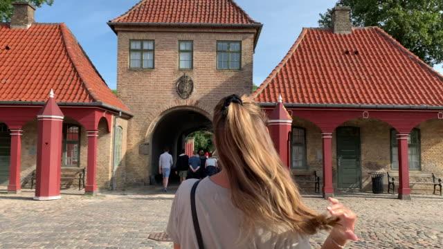 a young woman walks towards the entrance of kastellet (the citadel), copenhagen - öresundregion stock-videos und b-roll-filmmaterial