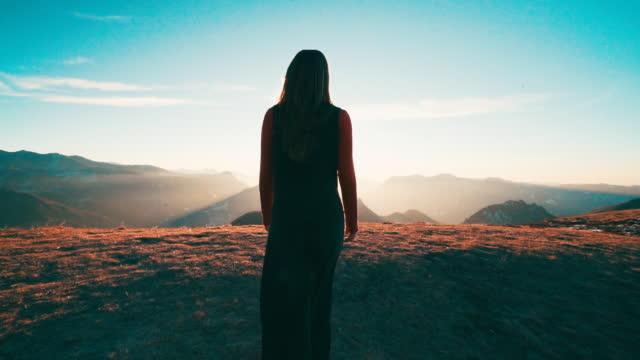 vídeos de stock, filmes e b-roll de jovem mulher caminha em direção a ponto de vista do nascer do sol - estupefação