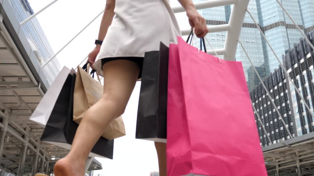 young woman walks with shopping bags - shopaholic stock videos & royalty-free footage