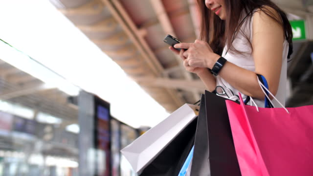 vidéos et rushes de jeune femme se promène avec des sacs à provisions - shopaholic