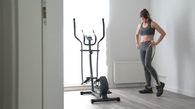 young woman warming up next to cross trainer at home - cross trainer stock videos & royalty-free footage