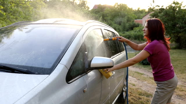 en ung kvinna tvättar en bil - biltvätt bildbanksvideor och videomaterial från bakom kulisserna
