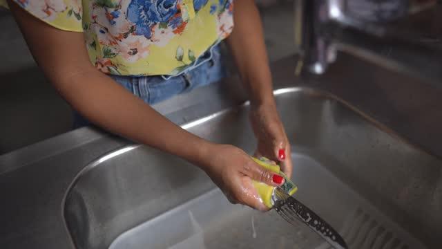 vídeos de stock, filmes e b-roll de jovem lavando pratos em casa - lavando louça