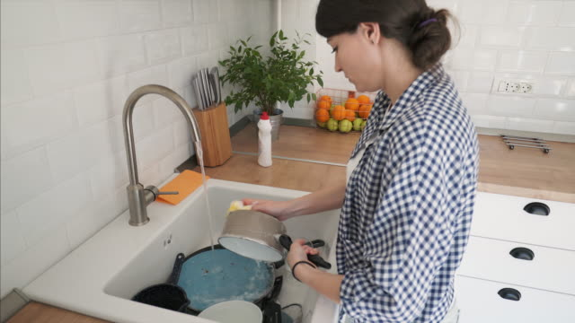 vídeos de stock e filmes b-roll de young woman washing dishes in the kitchen. - lava