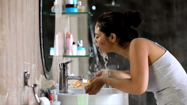 vidéos et rushes de young woman washing face in bathroom, delhi, india - lavabo