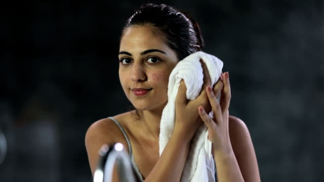 Young woman washing face in bathroom, Delhi, India