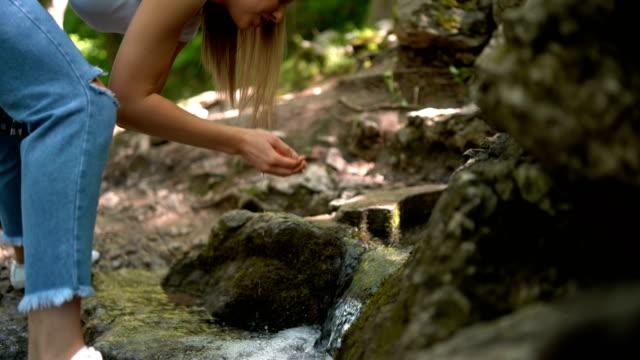 vídeos de stock, filmes e b-roll de face de lavagem da mulher nova no rio da montanha - área arborizada